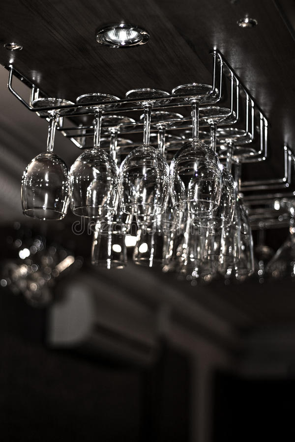 Bar glasses hanging on the rack stock image