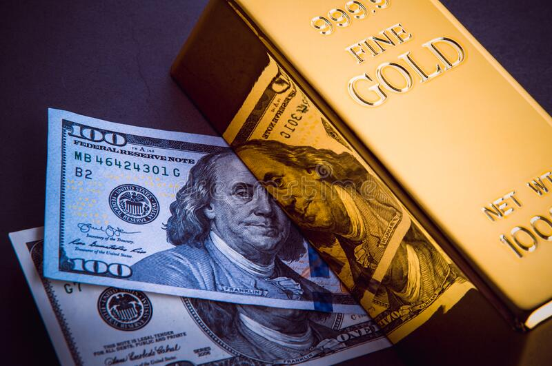 A bar of gold and a hundred-dollar bills.  stock photo
