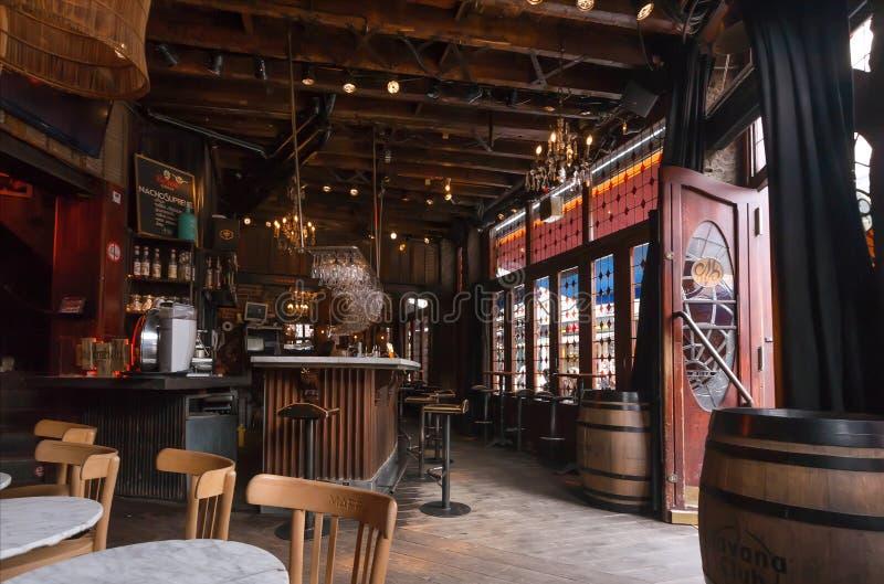 Bar met uitstekende houten meubilair en gebrandschilderd glasvensters die op drinkende bezoekers wachten stock foto's