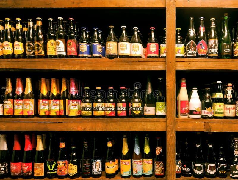 Bar met vele kleurrijke flessen van het bier van ambachtbelgi?, verschillende soorten en brouwerijen stock afbeeldingen