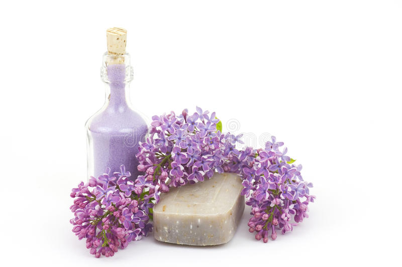 Bar of natural soap, bath salt and lilac flowers royalty free stock images