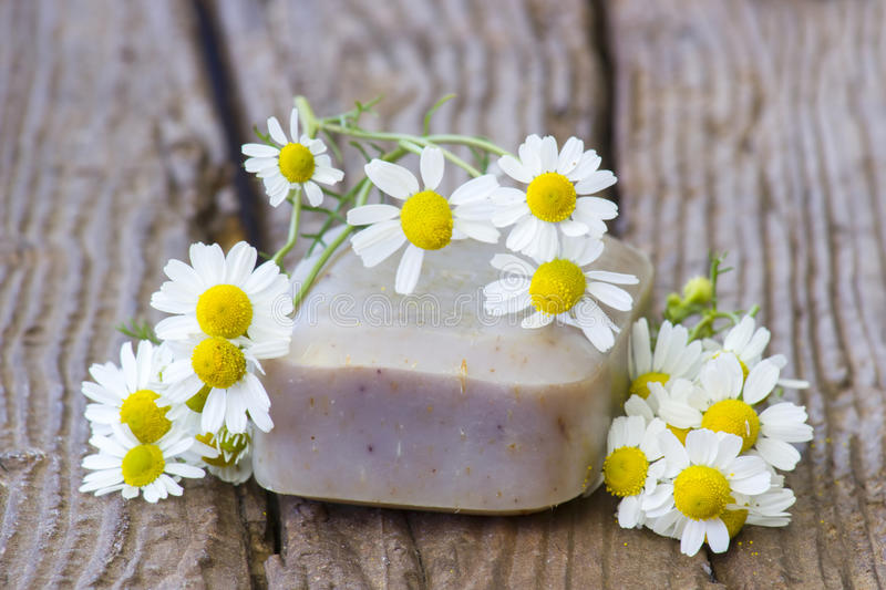 Bar of natural soap and chamomile flowers stock photos