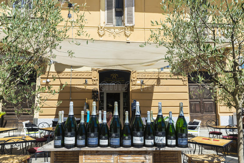 Bar in Olbia, Sardinia, Italy. Olbia, Italy - August 24, 2016: Bar in Olbia with Henriot champagne bottles with people drinking in a bar terrace in Sardinia royalty free stock photo