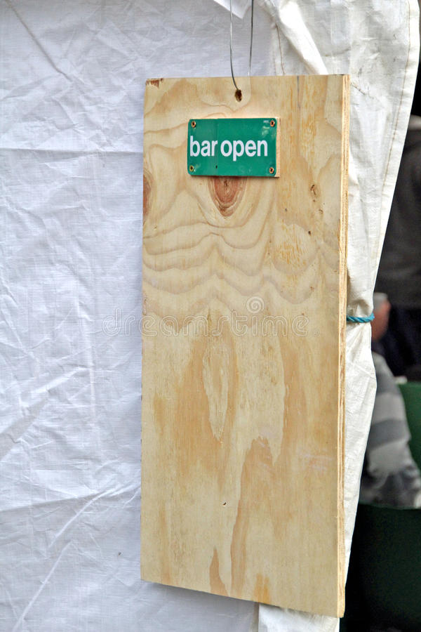 Bar open sign on tent. Photo of a bar open wooden sign outside a tent stock photos