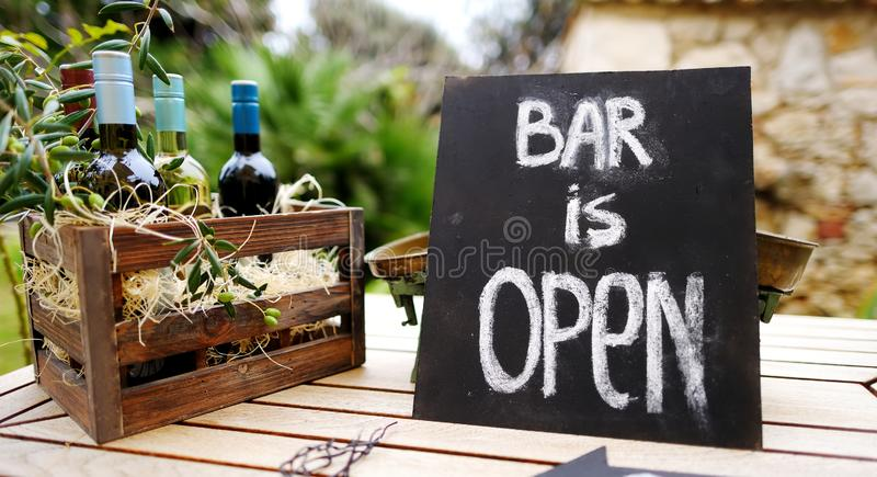 `Bar is open` sign and wooden crate full of wine bottles decorated with olive branches on a table. Festive party, weddin royalty free stock photography