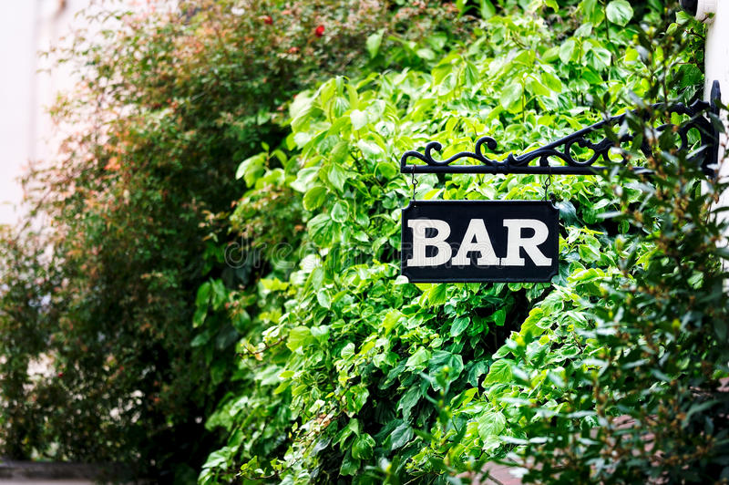 Bar signboard. On the corner of house near the trees stock photo