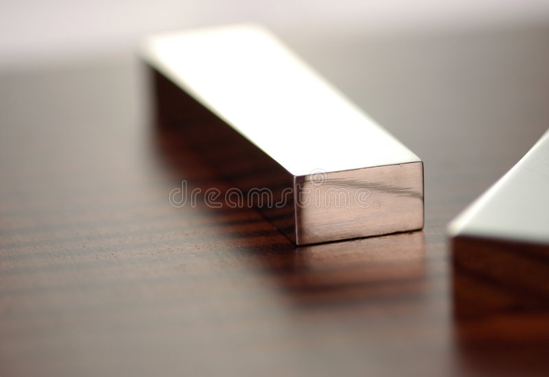 Bar of Silver. A silver bar sits in the middle of the frame with the corner of another in the front with very shallow depth of field royalty free stock image