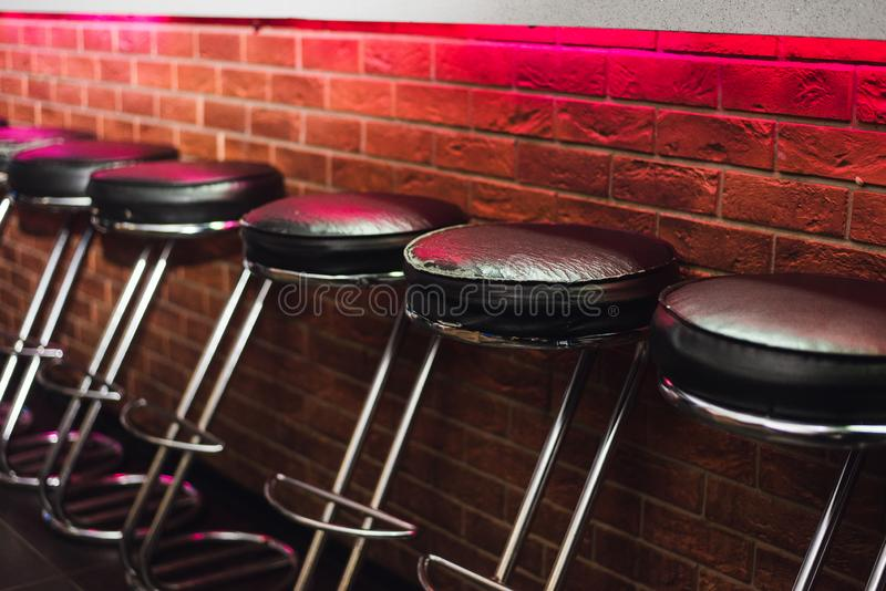 Bar stools at the counter in neon light. leather chairs at the bar in the nightclub stock image