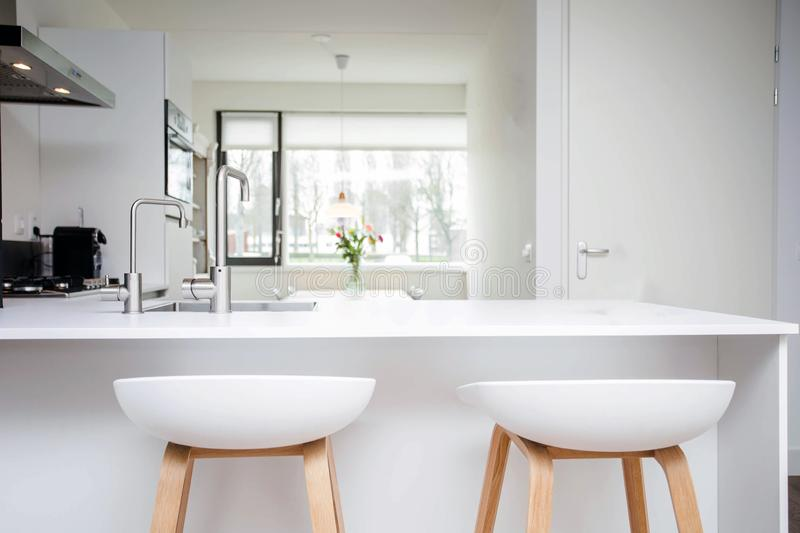 Bar stools by modern white kitchen island, new and clean modern design royalty free stock image