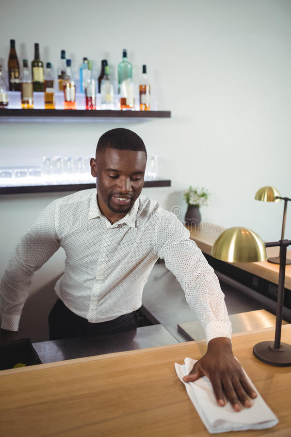 Bar tender cleaning bar counter in restaurant stock image