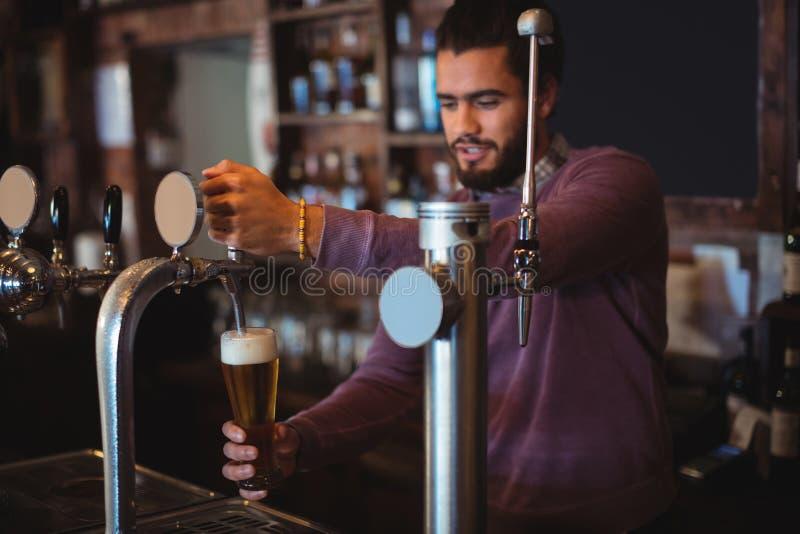 Bar tender filling beer from bar pump stock images