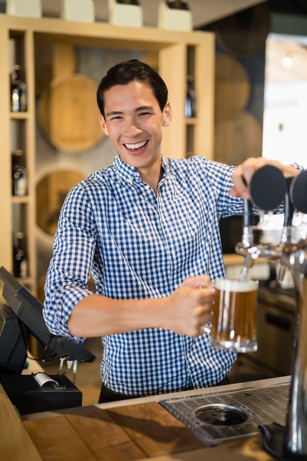 Bar tender filling beer from beer pump stock image