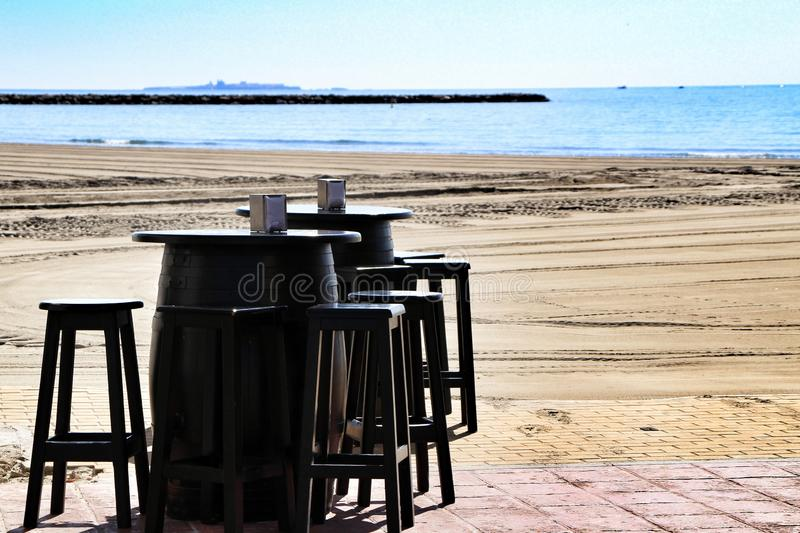 Bar with terrace on Santa Pola beach. Bar with empty terrace on Santa Pola beach in a sunny day side sand beautiful spain interior cloudy ocean relax shore table royalty free stock images