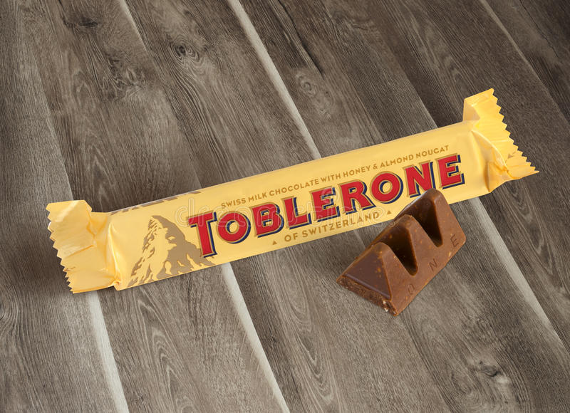 A bar of Toblerone. Chisinau, Moldova - June 14, 2016: A bar of Toblerone - Swiss milk chocolate with honey and almond nougat on a wood background. With clipping stock photography