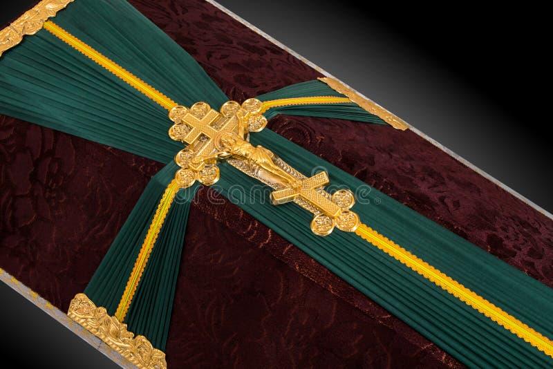 Bara chiusa coperta di panno marrone e verde decorato con l'incrocio dell'oro della chiesa su fondo di lusso grigio Primo piano illustrazione di stock
