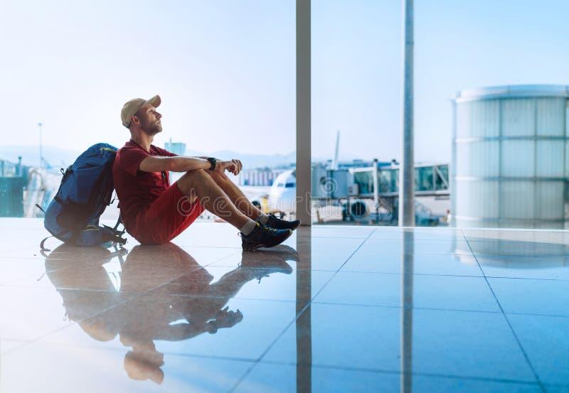 Bara fotvandrarehandelsresande som sitter på golvet för flygplatsterminal och det väntande på logiet på flygplan som förberedde s royaltyfri foto