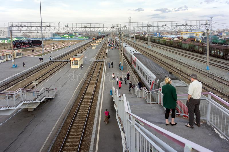 View from the rail-overroad bridge to the platform with a train and walking passengers, the railway station of the Siberian city. royalty free stock photo