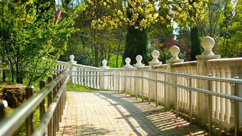 Barandilla blanca con las decoraciones de bolas en un parque tropical fotos de archivo