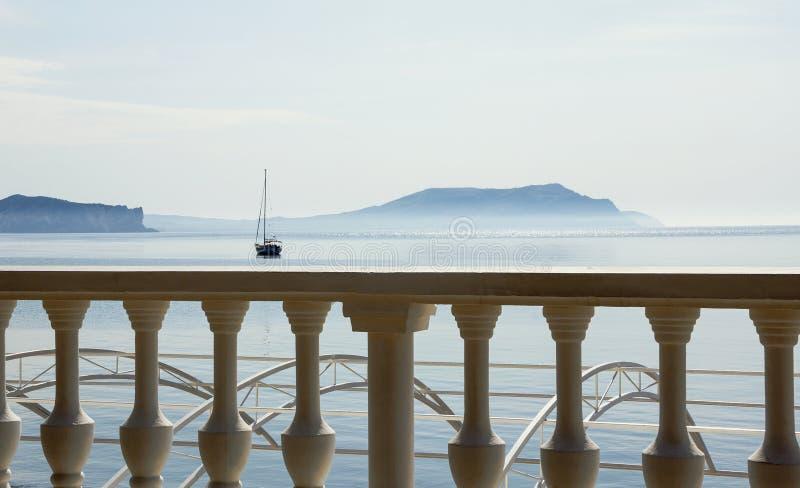 Barandilla blanca que pasa por alto la bahía, las montañas azules y un barco con un palo imagen de archivo libre de regalías