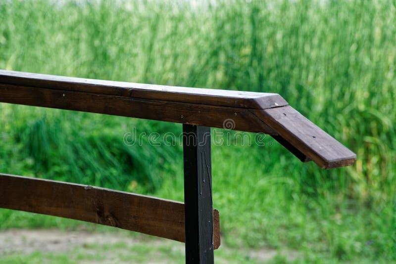 Barandilla de madera en parque público con el banco del césped y árbol verde, lugar para la relajación fotografía de archivo libre de regalías