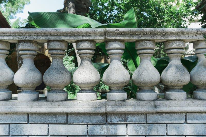 Barandilla gris vieja con las columnas y la verja de piedra fotos de archivo