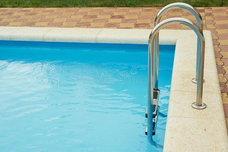 Barandillas del metal en la piscina La pendiente en el agua Vacaciones, descanso y relajación imágenes de archivo libres de regalías