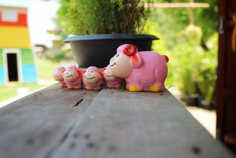 Barania rodziny grupa, piękna różowa ceramiczna lala, umieszczająca na starej drewnianej podłodze obraz stock