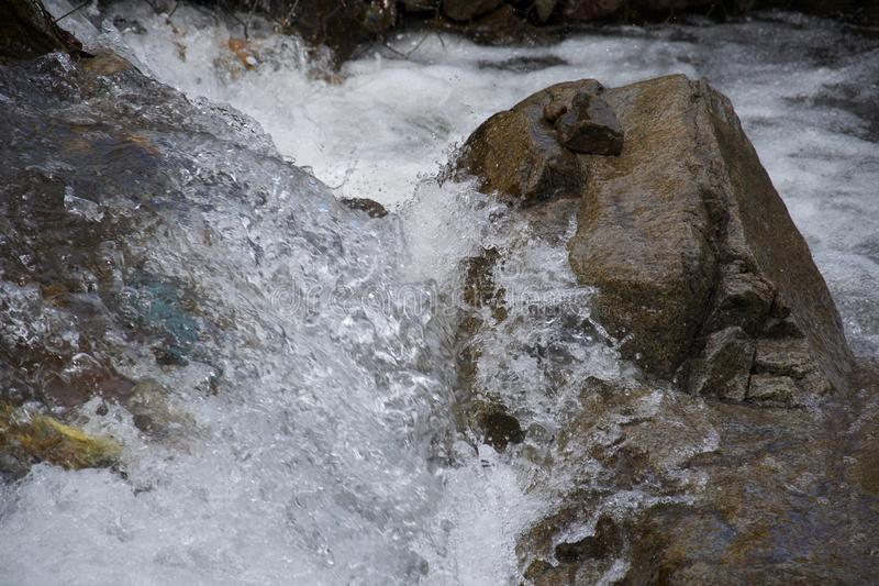 Barattes de l'eau autour d'une roche en rivière photo libre de droits