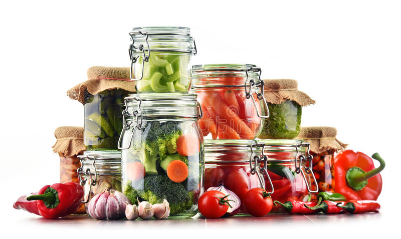 Barattoli con alimento marinato e le verdure crude isolati su bianco immagine stock