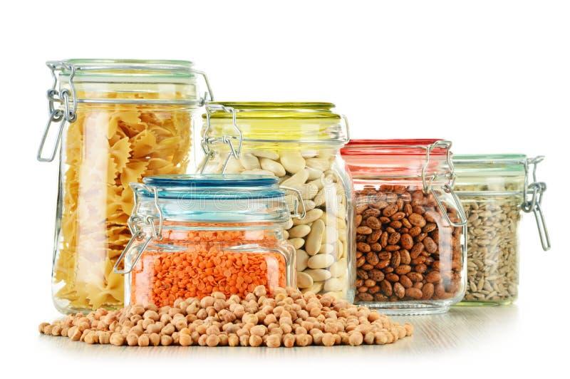 Barattoli con gli alimenti di grano su bianco fotografia stock