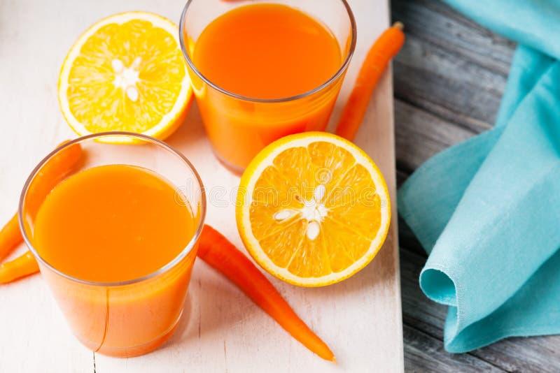 Barattoli con il succo di carota, la carota e l'arancia affettata fotografia stock