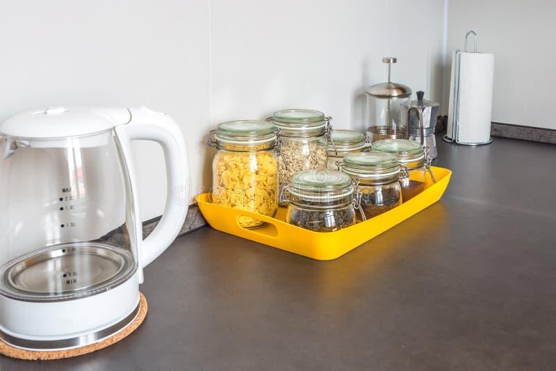 Barattoli d'annata alla moda di vetro con alimento e la teiera differenti nell'interno della cucina moderna in appartamento piano fotografia stock libera da diritti