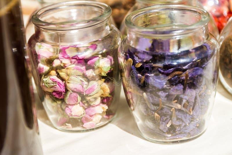Barattoli delle foglie di tè e dei fiori secchi fotografia stock libera da diritti