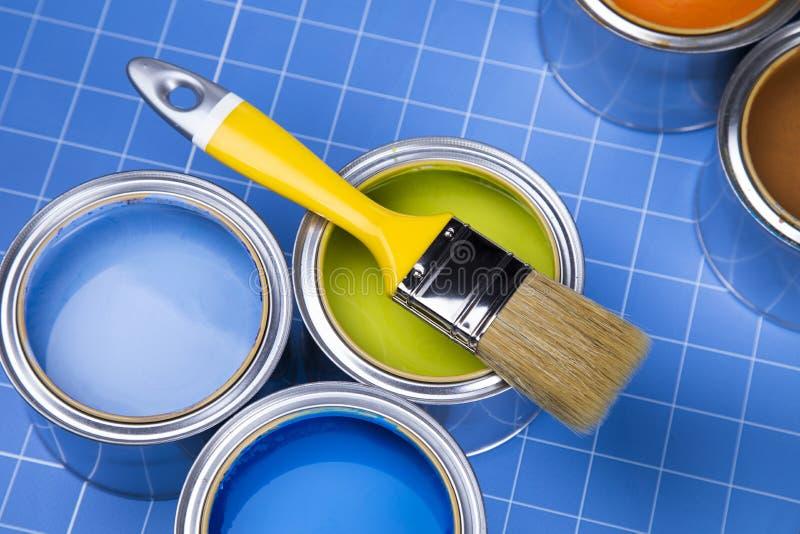 Barattoli di latta del metallo con la pittura di colore ed il pennello, fondo blu immagini stock