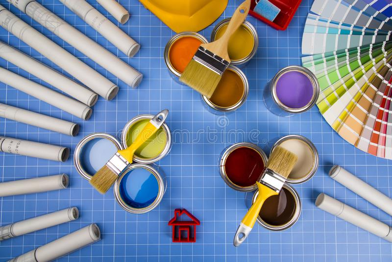 Barattoli di latta del metallo con la pittura di colore ed il pennello, fondo blu fotografia stock