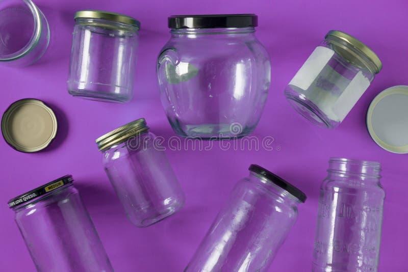 Barattoli di vetro con i coperchi, fondo porpora, disposizione del piano di vista superiore che ricicla concetto immagini stock