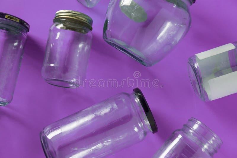 Barattoli di vetro con i coperchi, fondo porpora, disposizione del piano di vista superiore che ricicla concetto immagini stock libere da diritti