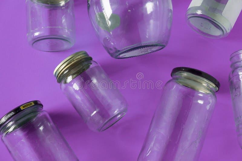 Barattoli di vetro con i coperchi, fondo porpora, disposizione del piano di vista superiore che ricicla concetto fotografia stock libera da diritti