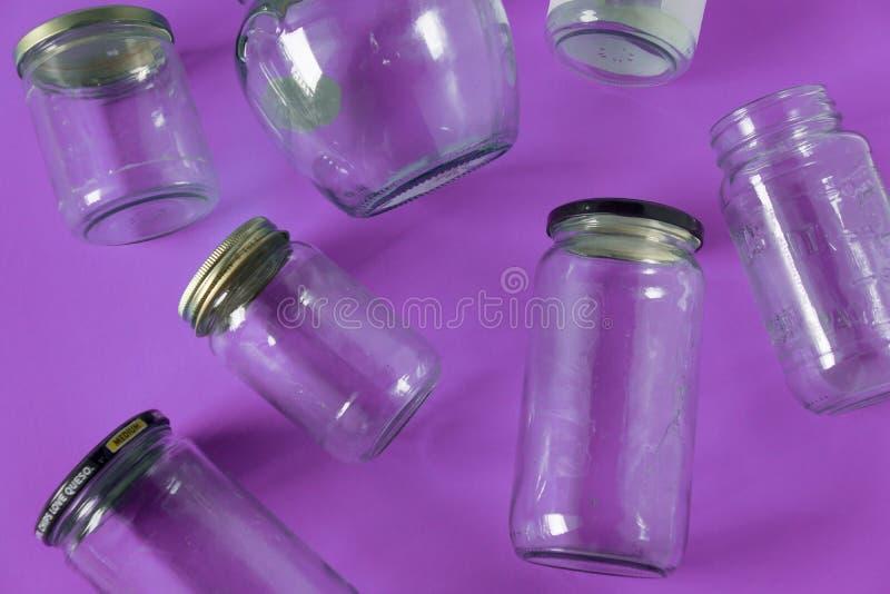 Barattoli di vetro con i coperchi, fondo porpora, disposizione del piano di vista superiore che ricicla concetto fotografie stock