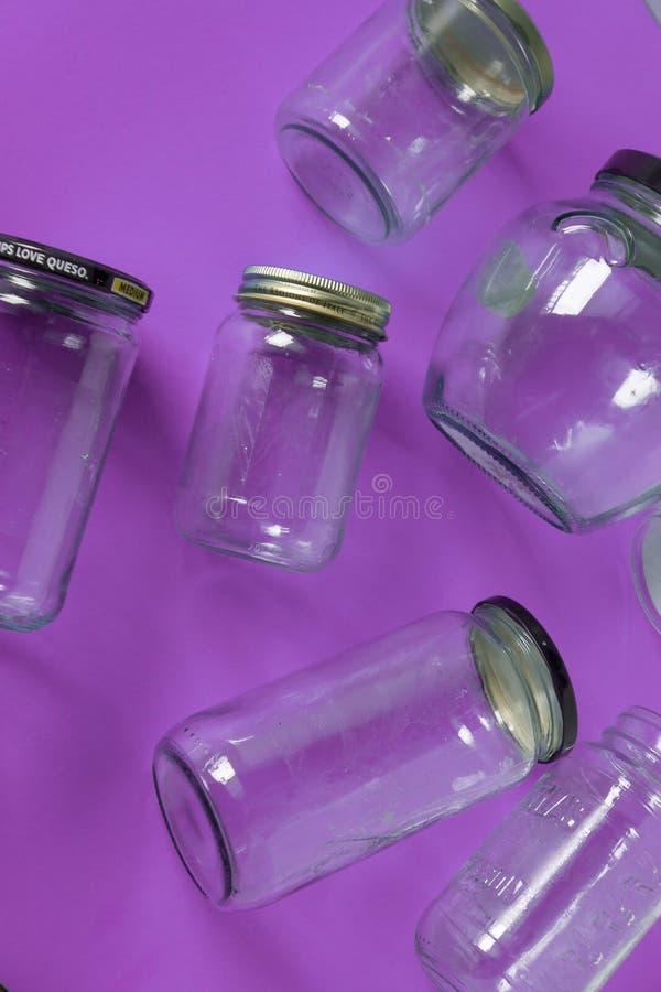 Barattoli di vetro con i coperchi, fondo porpora, disposizione del piano di vista superiore che ricicla concetto immagine stock libera da diritti