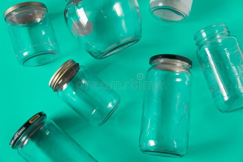Barattoli di vetro con i coperchi, fondo di verde dell'alzavola, disposizione del piano di vista superiore che ricicla concetto fotografia stock libera da diritti