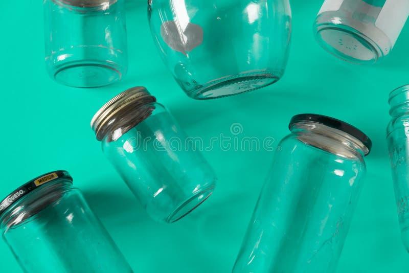 Barattoli di vetro con i coperchi, fondo di verde dell'alzavola, disposizione del piano di vista superiore che ricicla concetto fotografia stock