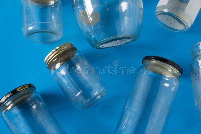 Barattoli di vetro con i coperchi su fondo blu, disposizione del piano di vista superiore che ricicla concetto fotografia stock libera da diritti