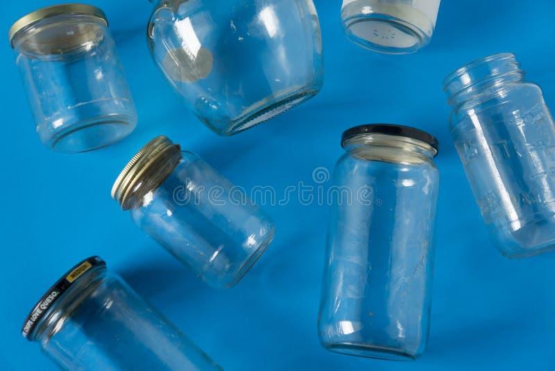 Barattoli di vetro con i coperchi su fondo blu, disposizione del piano di vista superiore che ricicla concetto fotografie stock libere da diritti