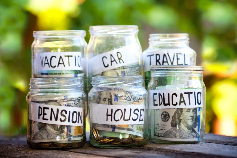 Barattoli di vetro con i dollari ed il testo: casa, automobile, viaggio, istruzione, pensione immagini stock libere da diritti