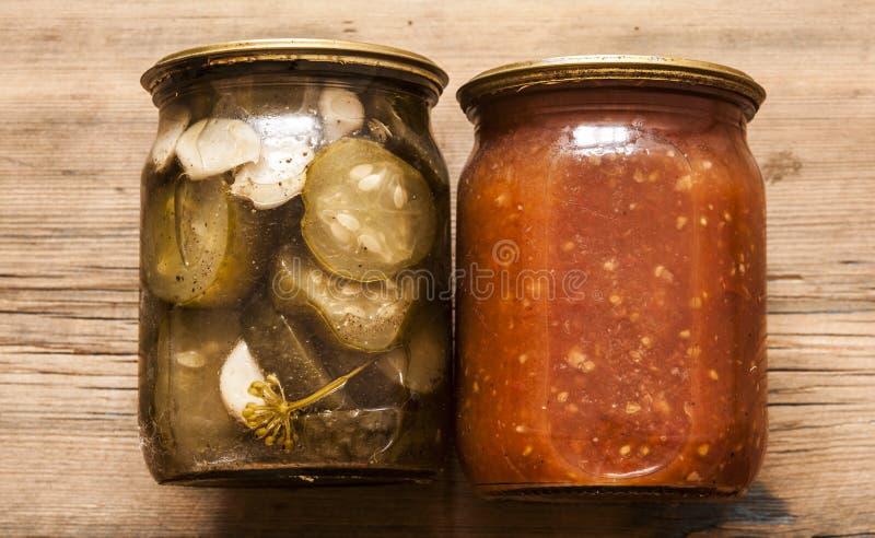 barattoli di vetro dei sottaceti casalinghi rustici, cetrioli del cetriolino, pomodoro immagini stock