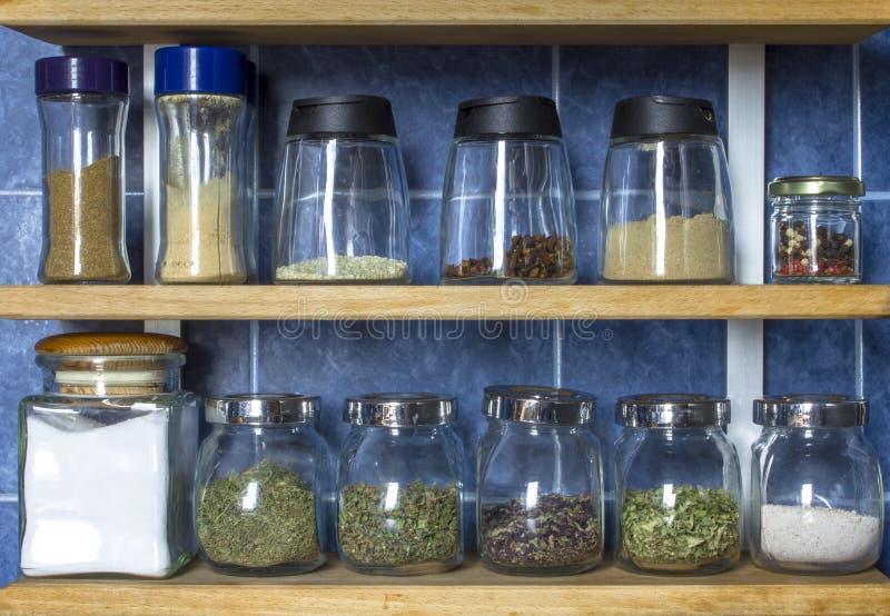 Barattoli di vetro trasparenti di varie forme e dimensioni con le varie spezie colorate sugli scaffali di legno contro una parete fotografia stock