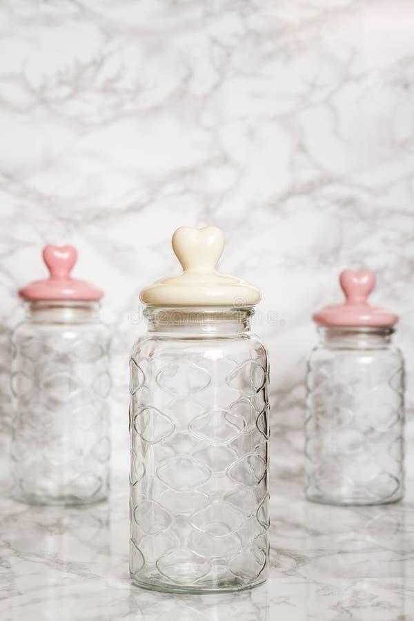 Barattoli di vetro vuoti su fondo di marmo bianco fotografia stock