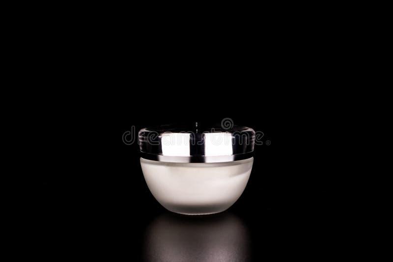 Barattolo bianco con crema su fondo nero fotografia stock libera da diritti