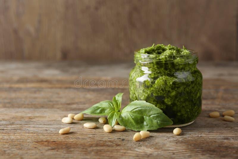 Barattolo della salsa di pesto con le foglie ed i pinoli del basilico sulla tavola di legno fotografia stock libera da diritti